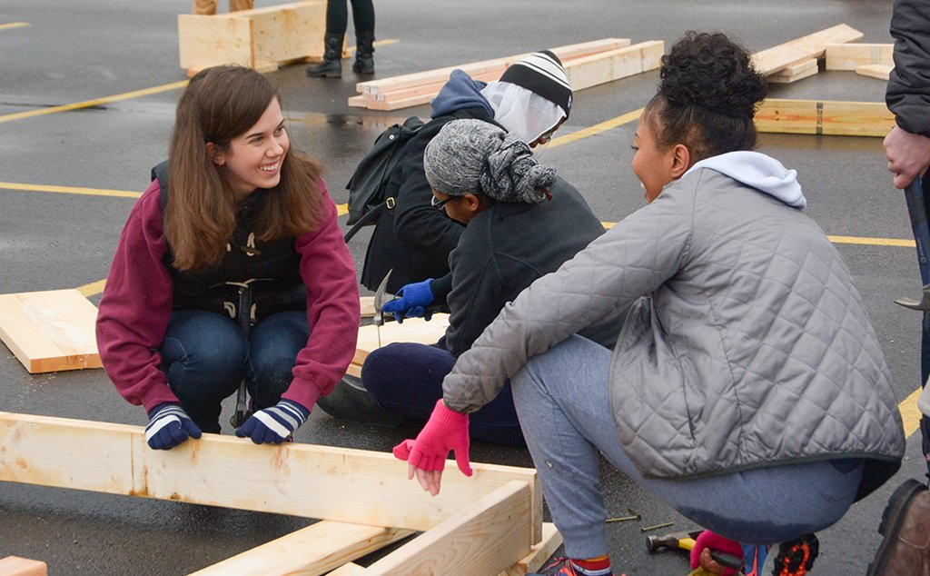 Students in a BW parking lot building a home for Habitat for Humanity.