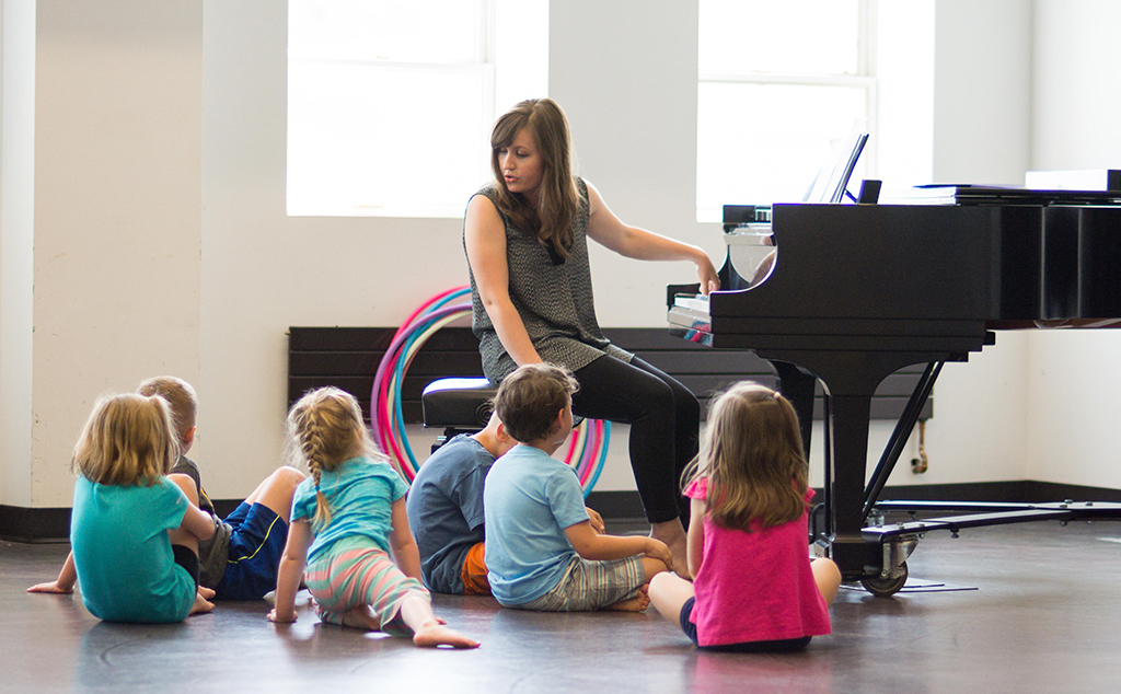Photo of a Dalcroze class, with the teacher at a piano and children sitting on the floor around her