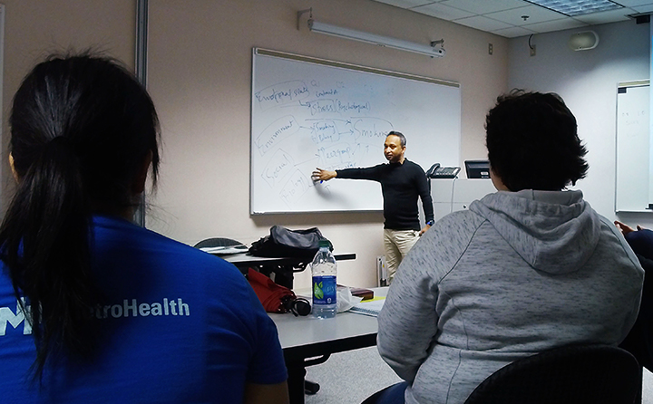 Photo of professor at whiteboard leading a lecture to MPH students
