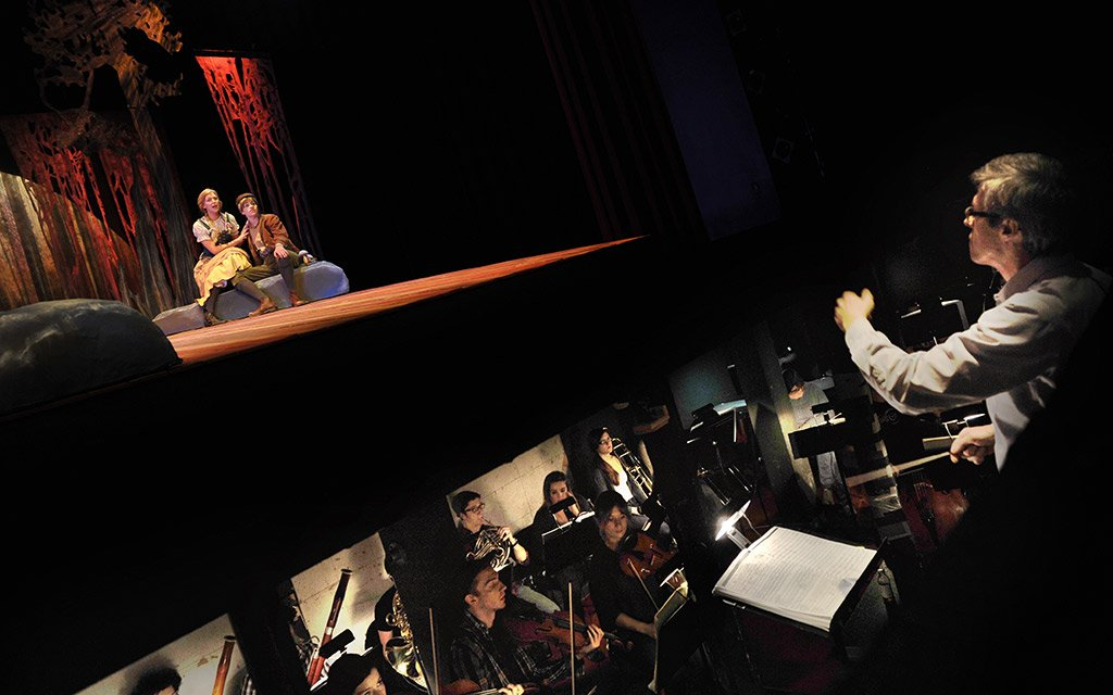 Music theater student perform while orchestra plays soundtrack in bit underneath stage