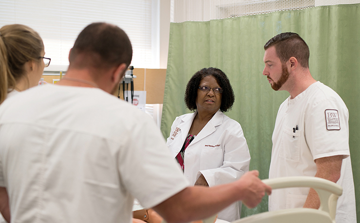 Three students talk with Betty Napoleon in a hospital setting