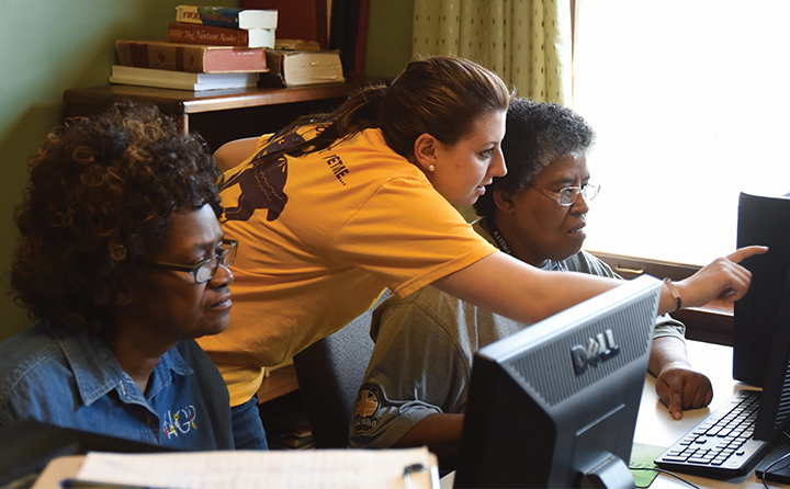 Photo of student helping two women on computers