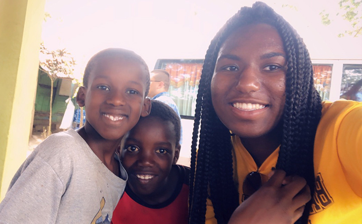 BW student Autumn Richards (right) with two children in the Dominican Republic on an Honors Program trip