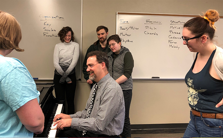 Honors students standing around BW professor playing piano in classroom