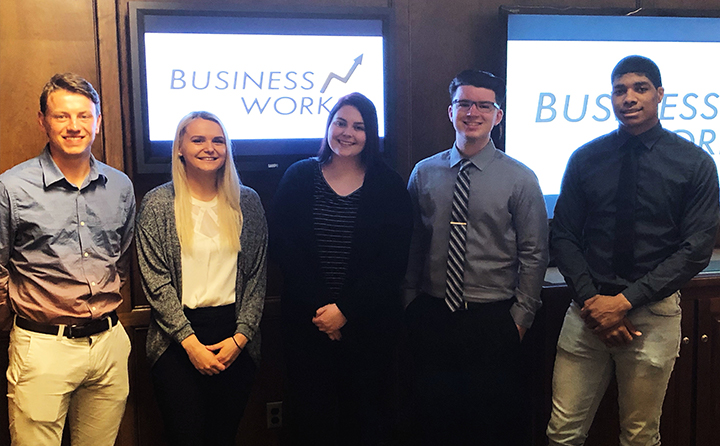 Photo of students standing in a conference room in front of TV screens with the Business Works logo