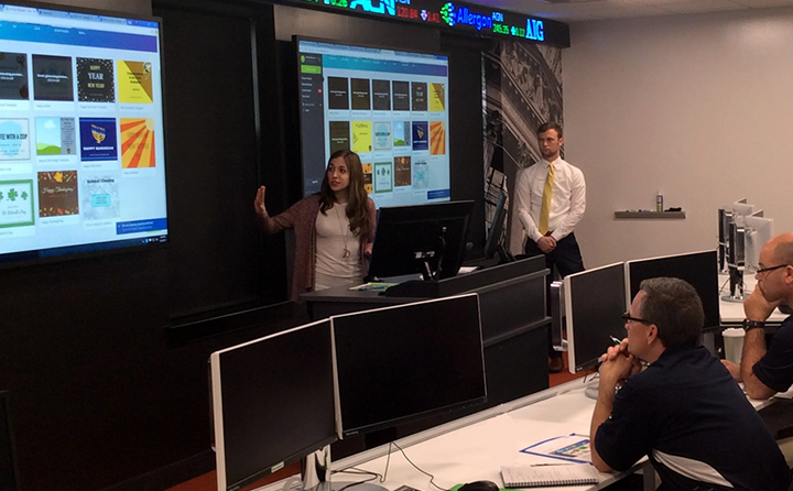 Photo of students giving a presentation in front of large screens