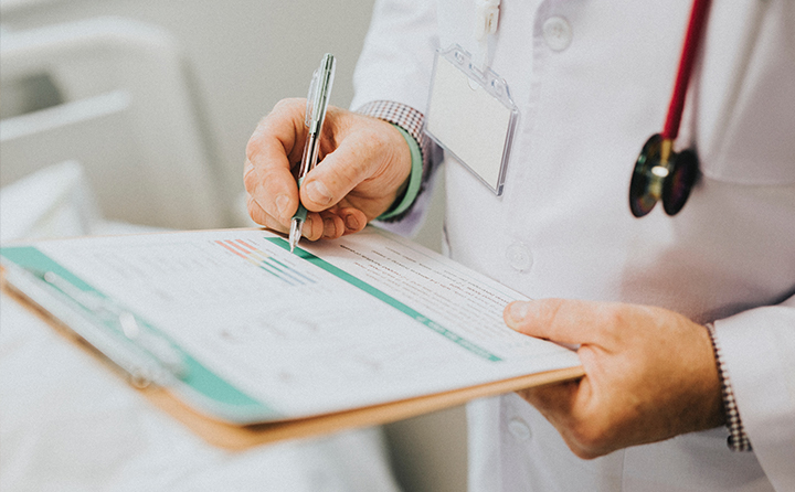 Photo of doctor writing on a chart