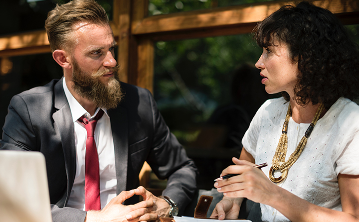 Photo of two people in business attire talking outside at a table