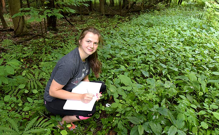 BW student Katie Swanson doing research in wooded area
