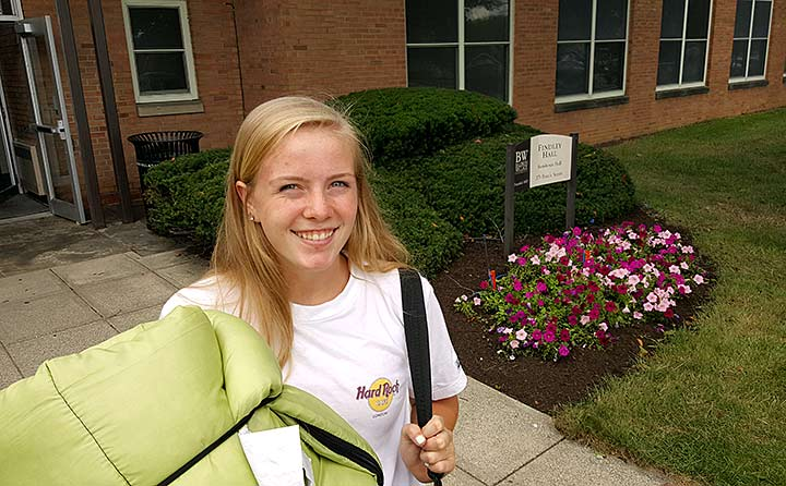 Photo of girl by residence hall on move-in day 2016