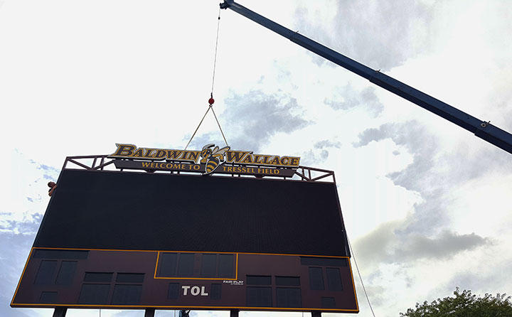 A crane hoists the top onto BW's new video scoreboard