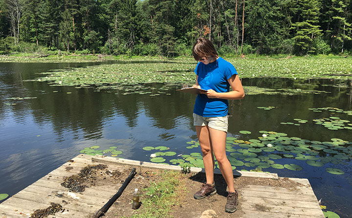 Biology and sustainability graduate, Claire Watts '17, of Medina, records water quality data at one of two lakes on the Richfield Preserve property.