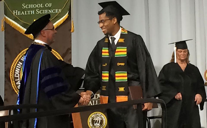 Samuel McIntosh congratulated by BW President Robert Helmer at his commencement