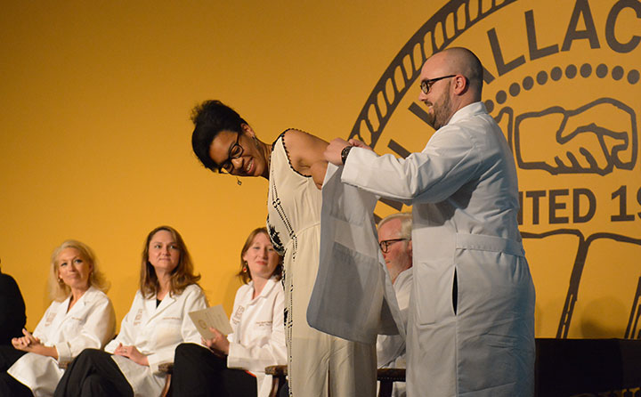 PA department chair Jared Pennington helps second-year student Joy Akuchie slip into a medical jacket and mark a milestone during the program's 2016 White Coat Ceremony.