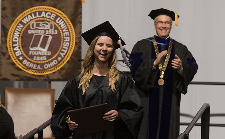 Baldwin Wallace University President Bob Helmer smiles as grad holds diploma