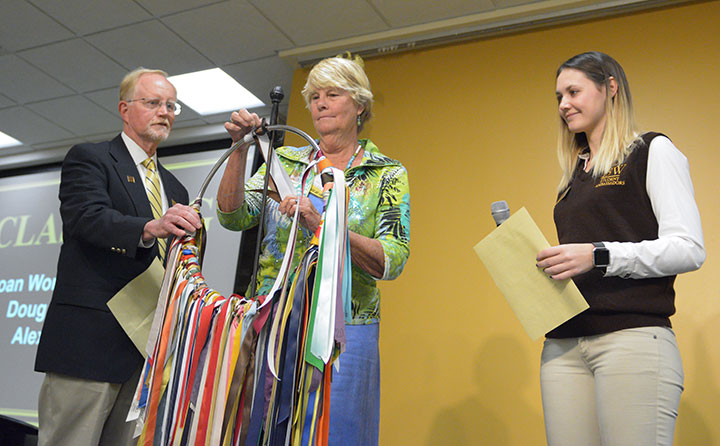 Members of the Baldwin Wallace Class of 1967 renew the class colors on the ring of ribbons