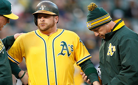 A's head trainer Nick Paparesta (right) examines the hand of Stephen Vogt (center) while manager Bob Melvin (left) looks on.