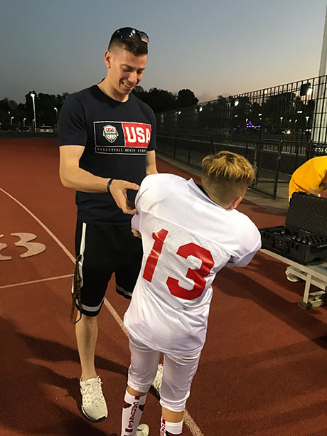 Adam Hoffman '18 assists a young  USA Football player with ta Catapult Tracking Device prior to the game.