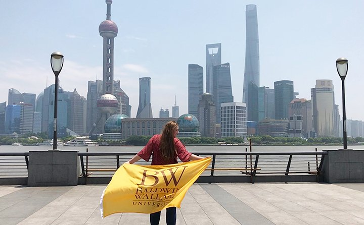 Business major Gwyn Dubel in China holding a Baldwin Wallace flag in front of a skyline.