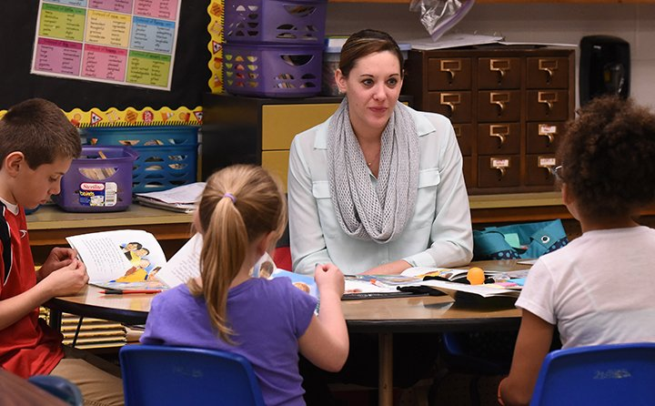Baldwin Wallace University education major Lauryn Fougerousse works with a third-grad reading group as part of her co-student teaching program with teacher Tony Zuccaro's third grade class at Brook Pa